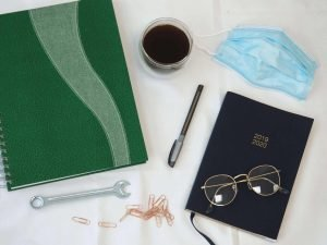 Work experience flat lay: Spanner, surgical mask, black coffee, diary, glasses, notebook etc.