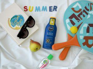 Summer flat-lay; suncream, sunglasses, scrapbook, paddle boards, fruit etc.